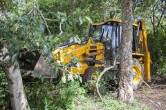 Sathyamangalam, Tamil Nadu, India - 24 giugno 2015: Un escavatore è visto ha parcheggiato fra gli alberi nella foresta di Sathyam Fotografia Stock Libera da Diritti