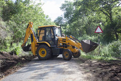 Sathyamangalam, Tamil Nadu, India - June 24, 2015: An excavator doing roadwork in the middle of the Sathyamangalam forest. Stock Photo