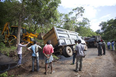 Sathyamangalam, Tamil Nadu, India - June 24, 2015: An excavator goes to lift a truck that has gone off the road, people watch on Royalty Free Stock Image
