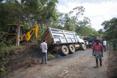 Sathyamangalam, Tamil Nadu, India - June 24, 2015: An excavator goes to lift a truck that has gone off the road, people watch on Stock Photo