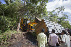 Sathyamangalam, Tamil Nadu, India - June 24, 2015: An excavator lifting up a truck that has gone off the road, people watch on Royalty Free Stock Image