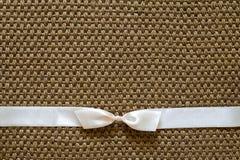 Satin bow on sisal background Stock Images