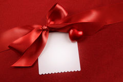 Satin bow and white card for gift on red Stock Images