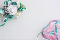 Satin braid of emerald and pink color intertwines on a white background. Near the wedding boutonniere. Satin braid of emerald and pink color intertwines on a Stock Photography