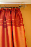 Satin Curtains. Beautiful orange satin curtains on a window in a living room Stock Photos