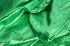 Satin Fabric. A rich green satin folded fabric background Royalty Free Stock Photos
