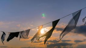 Satin flags waving in the wind at sunset stock images
