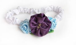 Satin headband with flowers. White satin headband with violet and blue flowers Royalty Free Stock Photo