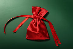 Satin red pouch isolated over green background Stock Photography