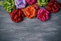 Satin ribbon gift bows of different colors. Some satin ribbon gift bows of different colors on a rustic gray wooden surface, with a blank space Royalty Free Stock Photography