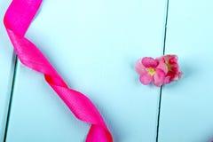 Satin ribbon and pink begonia flower. Stock Photo