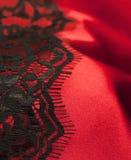 Satin rouge avec le lacet noir image stock