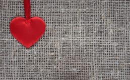 satin rouge facile de coeur se trouvant sur une toile de jute rugueuse Images libres de droits
