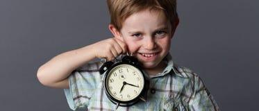 Satirical małe dziecko dokucza o czasie, pokazuje budzika Zdjęcie Royalty Free