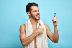 Satisfacen al hombre atractivo feliz con una nueva maquinilla de afeitar foto de archivo