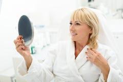 Satisfacen a la señora madura feliz con el tratamiento del skincare Imagenes de archivo