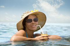 Satisfaction. Young woman in the pool with orange juice Royalty Free Stock Image