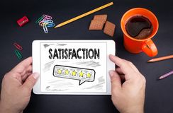 Satisfaction concept. Text and icon on tablet device royalty free stock photo