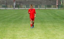 Satisfaction on football field. Happy little boy on football match Stock Photo