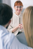 Satisfaction good marital therapist is associated with the satisfaction of couple. Smiling psychotherapist looks happy on snuggled couple during marriage therapy Royalty Free Stock Photos