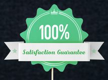 100% satisfaction guarantee badge cut from cardboard. And paper on a wooden stick. Green banner, seal and ribbon for business website to promise customer the Royalty Free Stock Photo