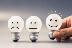Satisfaction Light Bulb. Hand choose a smile light bulb from satisfaction evaluation Stock Photos
