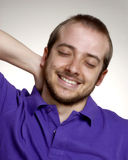 Satisfaction man. Expressive and happy young man portrait.Young man touching his neck Royalty Free Stock Photos