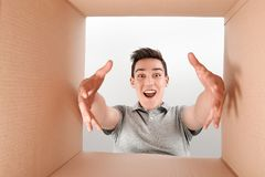 Satisfaction is a rating. Surprised boy opening box and looking inside. The package, delivery, surprise, gift, lifestyle stock photos