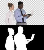 Satisfait de leur homme et femme de travail regardant dans l'ordinateur portable, Alpha Channel photographie stock libre de droits