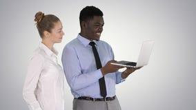 Satisfait de leur homme et femme de travail regardant dans l'ordinateur portable sur le fond de gradient images stock