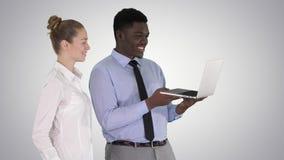 Satisfait de leur homme et femme de travail regardant dans l'ordinateur portable sur le fond de gradient clips vidéos