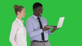 Satisfait de leur homme et femme de travail regardant dans l'ordinateur portable sur un écran vert, clé de chroma clips vidéos