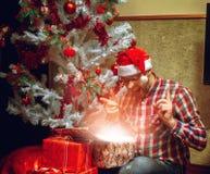 Satisfecho con su inconformista del regalo de Navidad en el sombrero de santa Imagenes de archivo