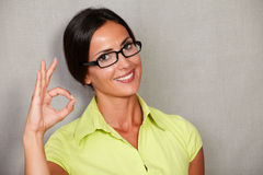 Satisfied adult female smiling with ok sign Stock Photography