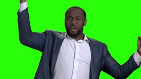 Satisfied afro american businessman on green screen. Joyful afro american man in formal wear raised hands on chroma key background, slow motion stock video footage