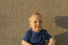 Satisfied baby boy Against the background of a concrete wall. Infant kid with unusual shadows on his face Stock Photos