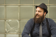 Satisfied Bearded Man. Well dressed happy bearded man sits against a glass building Stock Photo