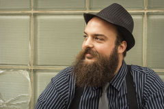 Satisfied Bearded Man. Well dressed happy bearded man sits against a glass building Stock Image