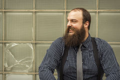 Satisfied Bearded Man. Well dressed happy bearded man sits against a glass building Stock Photos