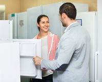 Satisfied beautiful couple looking at large fridges Stock Images