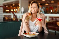 Satisfied beautiful young woman with a smile eating a hamburger. And drinking cola indoors royalty free stock photo
