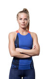 Satisfied Blue eyed blond girl. With tail hair in sportswear with crossed arms and front standing on white isolated background Stock Photography