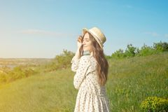 Satisfied brunette in a long summer dress wearing a straw hat is standing in the tall grass with her arms raised facing the royalty free stock photography