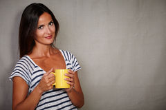 Satisfied brunette woman holding coffee cup. Satisfied brunette woman in blue shirt holding coffee cup while looking at camera Royalty Free Stock Photo