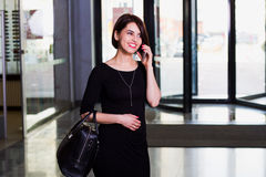 Satisfied   business lady in Shopping Mall, talking on the phone. Attractive business lady in Shopping Mall, emotionally talking on the phone Royalty Free Stock Photography