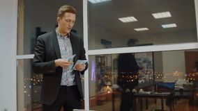 Satisfied business manager counting money bonus from stack in business office. Successful businessman sharing money banknotes near window in evening office stock video footage