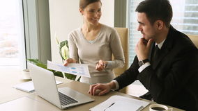 Satisfied business partners handshaking on meeting after discussing progress report. Male and female young business partners handshaking, satisfied by increased stock footage