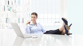 Satisfied business smiling woman in office with computer and fee Stock Image