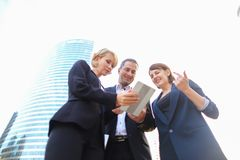 Happy business team members talking outside in  . Satisfied business team members speaking outdoors in  . Concept of biz partners enjoying successful result Stock Image