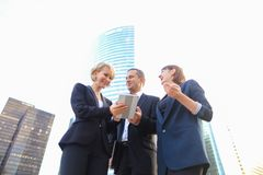 Happy business team members talking outside in  . Satisfied business team members speaking outdoors in  . Concept of biz partners enjoying successful result Royalty Free Stock Photos
